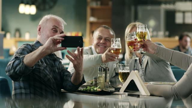 熟女のお友達がレストランで selfie を引き継ぐ - 食事する点の映像素材/bロール