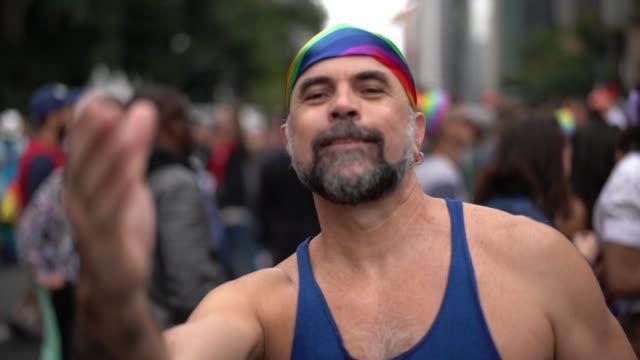 mature gay man beckoning at gay parade - 50 54 lata filmów i materiałów b-roll