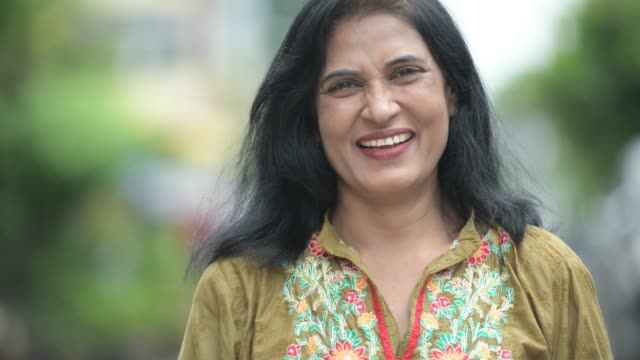 mature happy beautiful indian woman smiling in the streets outdoors - hindus filmów i materiałów b-roll