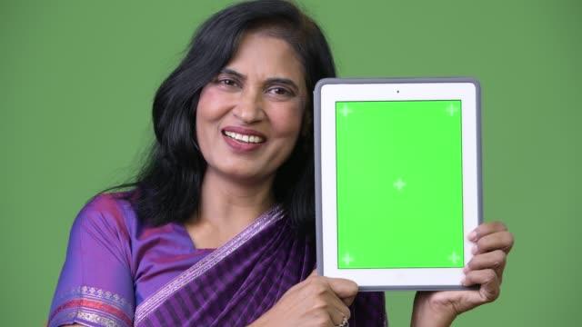 mature happy beautiful indian woman smiling while showing digital tablet - sari filmów i materiałów b-roll