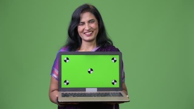 mature happy beautiful indian woman smiling while showing laptop - sari filmów i materiałów b-roll