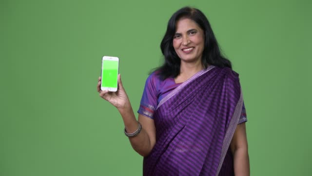 mature happy beautiful indian woman smiling while showing phone - sari filmów i materiałów b-roll
