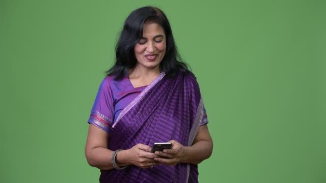 mature happy beautiful indian woman using phone - sari filmów i materiałów b-roll