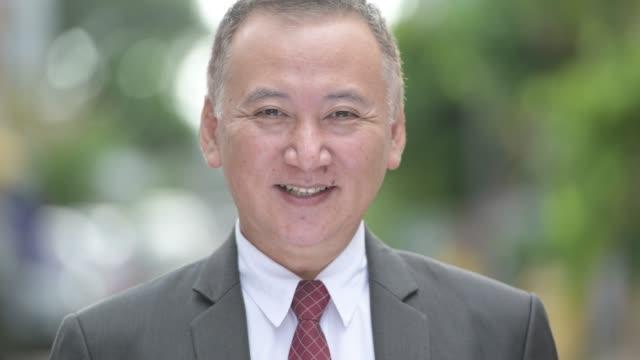 屋外の通りに笑みを浮かべて成熟した幸せな日本のビジネスマン - ビジネスマン 日本人点の映像素材/bロール