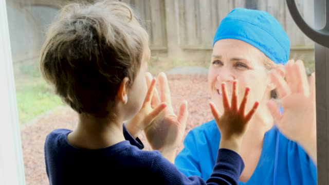 mature healthcare worker posing seeing her son with a window glass separating them to avoid possible contagion - hand on glass covid video stock e b–roll