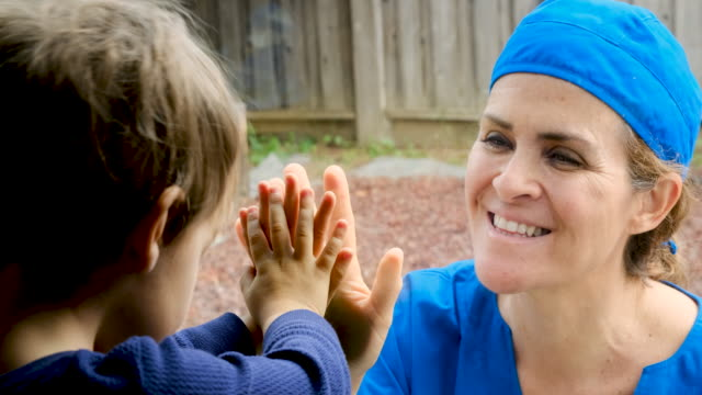 mature healthcare worker posing seeing her son with a window glass separating them to avoid possible contagion - covid 19 stock videos & royalty-free footage