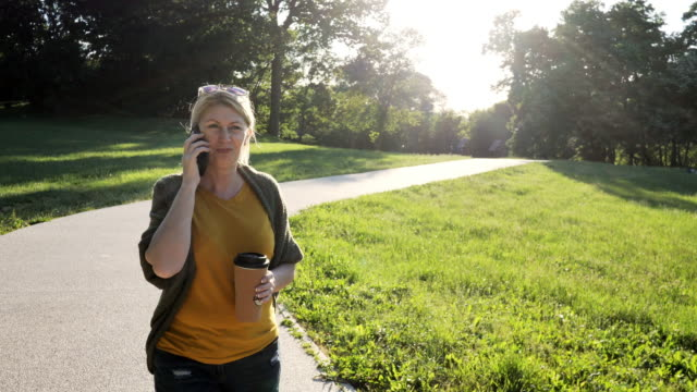Mature healthy woman outdoors on spring day in park using phone and talking