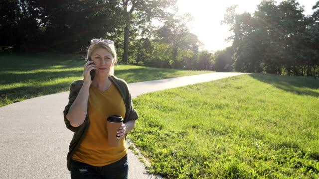 gammal frisk kvinna utomhus på vårdagen i parken med hjälp av telefon och prata - naturparksområde bildbanksvideor och videomaterial från bakom kulisserna