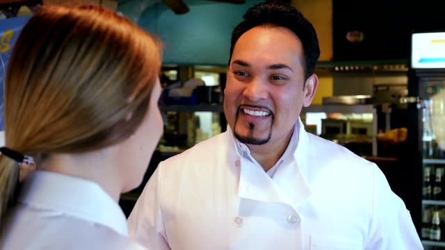 Mature Hispanic chef in Tex-Mex restaurant, training waitress in kitchen video