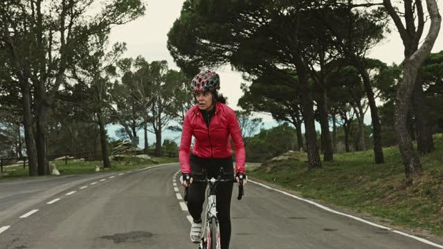Mature Hispanic Female Cyclist Riding Uphill on Coastal Road