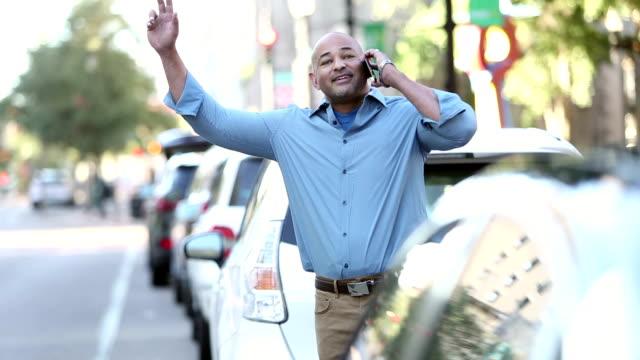 vidéos et rushes de homme hispanique mûr dans la ville sur le téléphone, saluant le taxi - homme faire coucou voiture