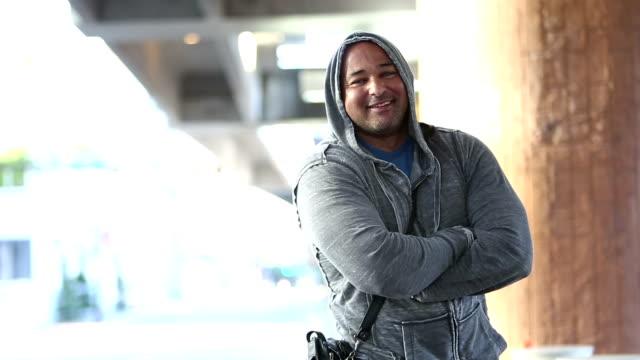 Mature Hispanic man in city waiting, turns to camera