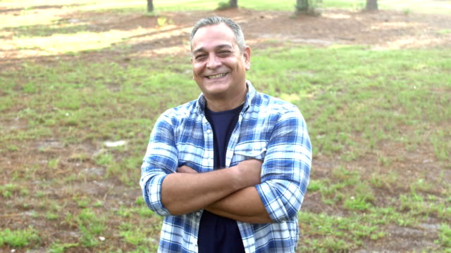 Mature Hispanic man standing in park A mature Hispanic man in his 50s with gray hair, standing in the  park looking at the camera. He is smiling, then crosses his arms. plaid stock videos & royalty-free footage