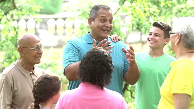 reifen hispanic mann mit seinem multi-generationen-familie - storytelling videos stock-videos und b-roll-filmmaterial