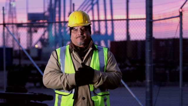 Mature Hispanic man working at shipping port, serious A mature Hispanic man in his 50s, wearing protective workwear including a hardhat, safety vest and safety glasses, standing with a serious expression at a shipping port, looking at the camera. Gantry cranes and cargo containers are in the background. manual worker stock videos & royalty-free footage