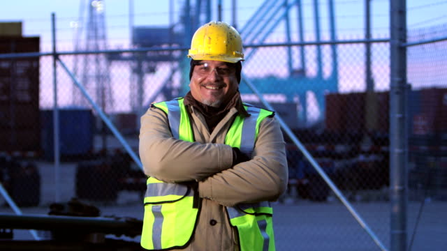 Mature Hispanic man working at shipping port, smiling A mature Hispanic man in his 50s, wearing protective workwear including a hardhat, safety vest and safety glasses, standing at a shipping port, smiling at the camera. Gantry cranes and cargo containers are in the background. work helmet stock videos & royalty-free footage