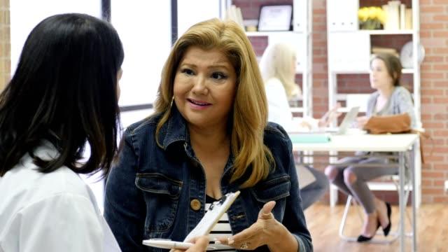 Mulher madura hispânico discute os sintomas com o médico dela - vídeo