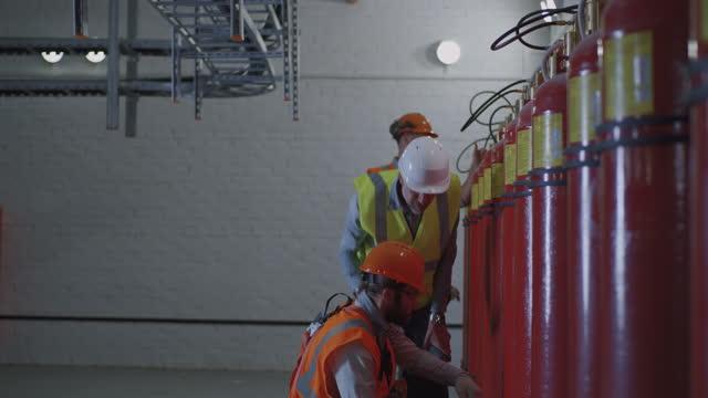 ispettore maturo che controlla i lavoratori vicino agli estintori - ispettore della qualità video stock e b–roll