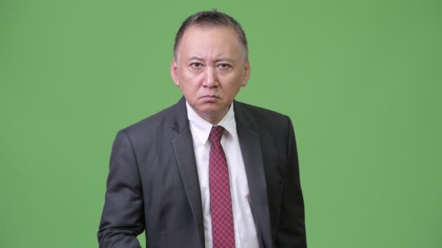 Mature Japanese businessman using magnifying glass Studio shot of mature Japanese businessman against chroma key with green background magnifying glass stock videos & royalty-free footage