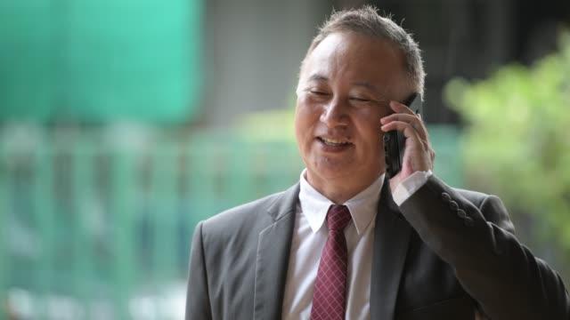 屋外の路上で携帯電話を使用して成熟した日本のビジネスマン - ビジネスマン 日本人点の映像素材/bロール