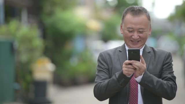 屋外の路上で携帯電話を使用して成熟した日本のビジネスマン - スマートフォン点の映像素材/bロール