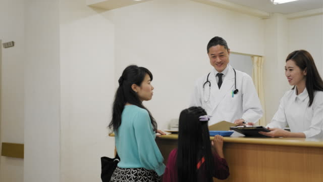 Mature Japanese woman talking to the female nurse at the registration desk in the hospital video