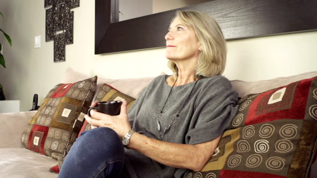 Mature lady enjoying a cup of coffee video