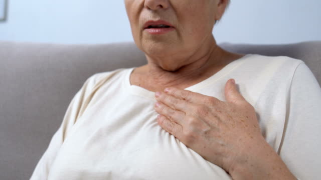vídeos de stock e filmes b-roll de mature lady hardly breathing, holding hand on chest, risk of heart attack - ataque cardíaco