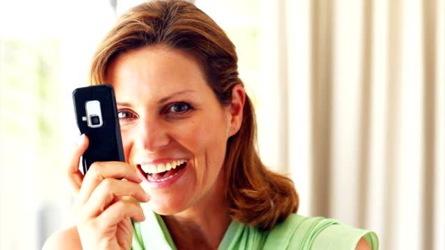 matura donna utilizzando un cellulare telecamera - femminilità video stock e b–roll