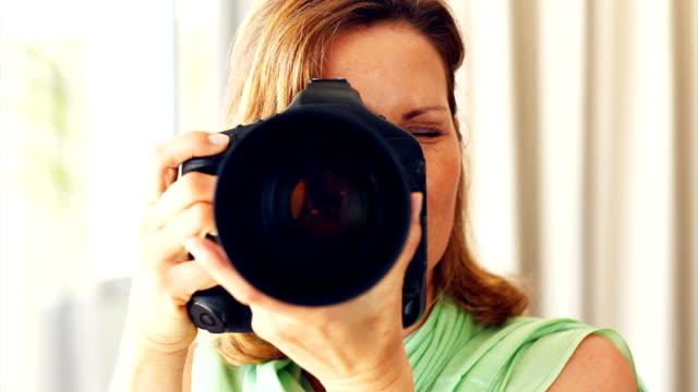 dojrzała kobieta za pomocą aparatu cyfrowego - kobiecość filmów i materiałów b-roll