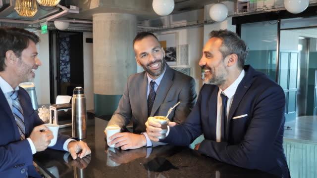 mature latin business people enjoying coffee break - argentyna filmów i materiałów b-roll