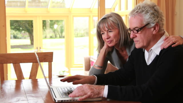 Mature male and female looking at laptop video