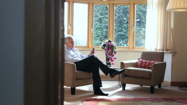 mature male answering phone call - endast en medelålders man bildbanksvideor och videomaterial från bakom kulisserna