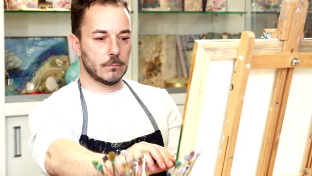 mature male artist working on a painting at his art studio - solo un uomo maturo video stock e b–roll