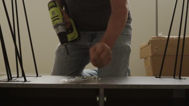 vidéos et rushes de mature homme diy meubles ensemble avec batterie power tool drill 4k série vidéo - bureau ameublement