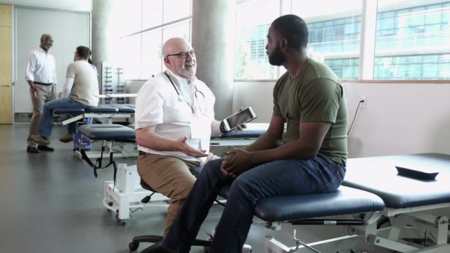olgun erkek doktor onun sağlığı hakkında askeri asker ile görüşmeler - tıbbi klinik stok videoları ve detay görüntü çekimi