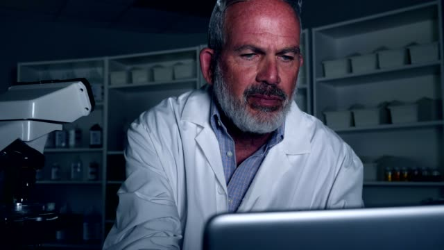 Mature male scientist works in a lab at night