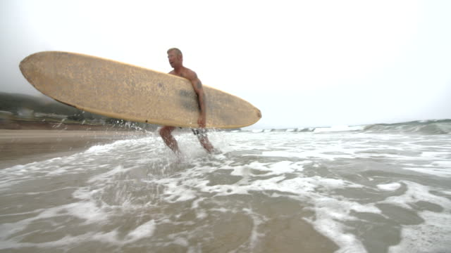 a mature male surfer leaving the ocean waves with his longboard. - зрелые мужчины стоковые видео и кадры b-roll