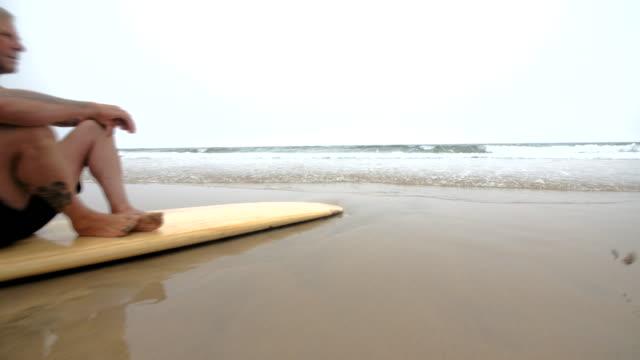 Ein reifer männlicher Surfer Blick auf das Meer. – Video