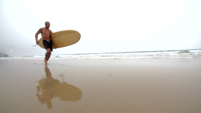 A mature male Surfer running along a glassy sandy beach with a reflection. video