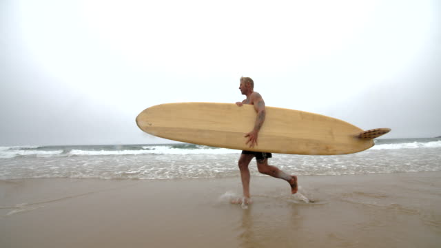 A Mature male surfer running through the Surf with his longboard. video