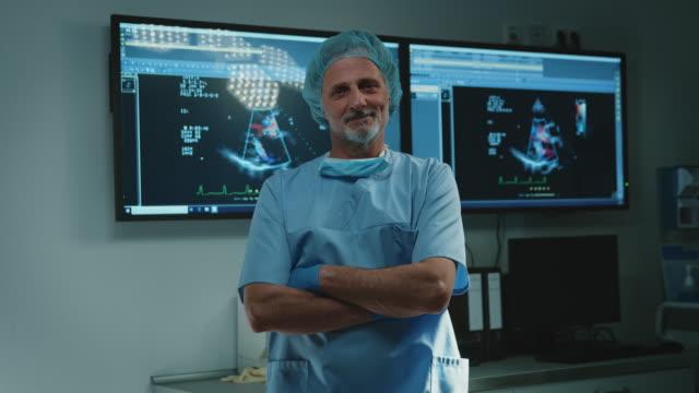 vídeos de stock e filmes b-roll de mature male surgeon with arms crossed at hospital - instrumento para diagnóstico