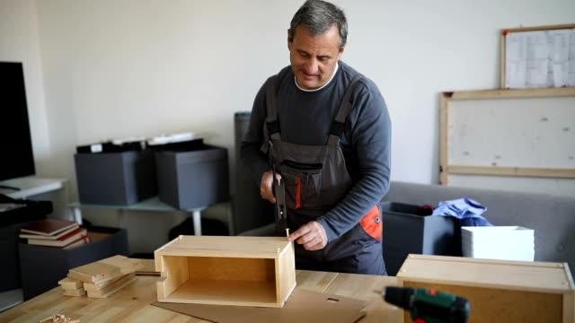 Mature man assembling wooden drawer