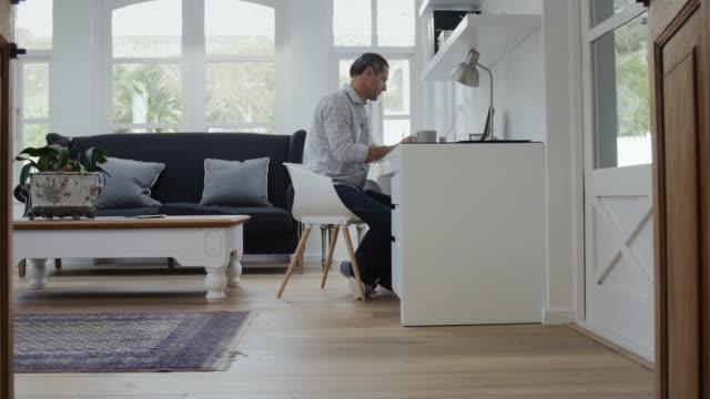 mature man at desk working from home - uomini maturi video stock e b–roll