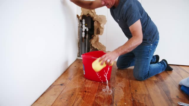 Mature Man At Home Mopping Up Water From Leaking Pipe
