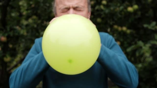 vídeos de stock, filmes e b-roll de homem maduro, soprando um balão - soprando
