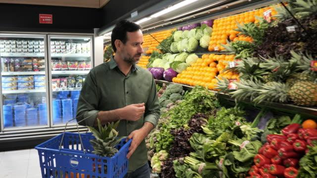 Mature man buying fruit in supermarket