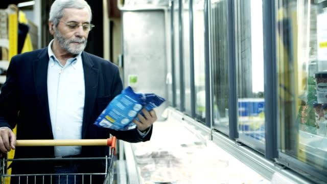 mature man buying goods in store - замороженные продукты стоковые видео и кадры b-roll