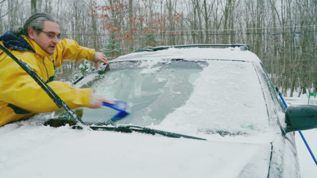 Mature man cleaning a car from snow and ice, scraping the windshield with icescraper.