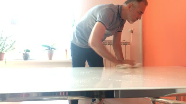 vidéos et rushes de mature man nettoyage table à manger à la maison - un seul homme d'âge mûr